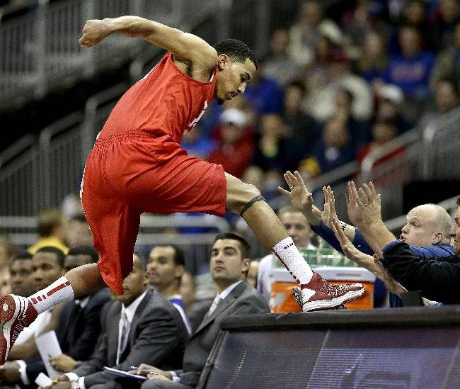 New Mexico's Kendall Williams leaps onto a table after saving a ball from going out of bounds during the second half of an NCAA college basketball game against Kansas, Saturday, Dec. 14, 2013, in Kansas City, Mo. Kansas won 80-63
