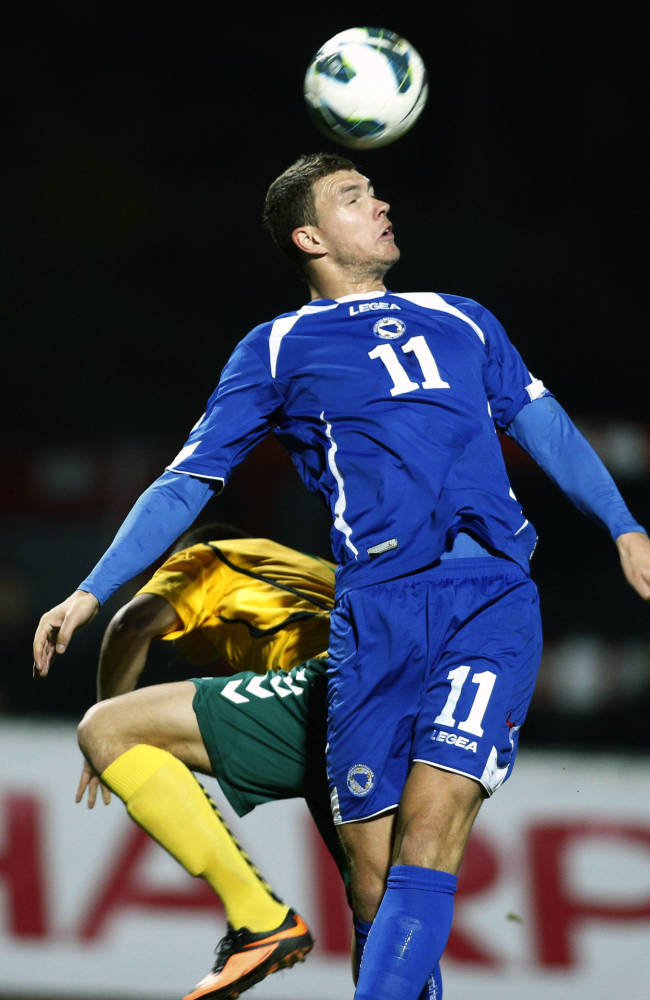 Bosnia's Edin Dzeko, front, heads the ball during the World Cup group G qualifying soccer match between  Lithuania and Bosnia  in Kaunas, Lithuania, Tuesday, Oct. 15, 2013