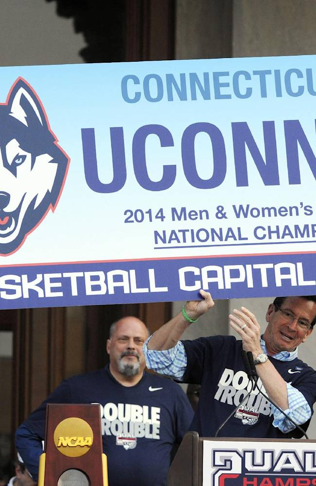 Connecticut Gov. Dannel P. Malloy, center, Connecticut women's basketball coach Geno Auriemma, left, and men's basketball coach Kevin Ollie celebrate UConn's titles in the NCAA women's and men's tournaments, during a rally at the State Capitol in Hartford, Conn., on Sunday, April 13, 2014