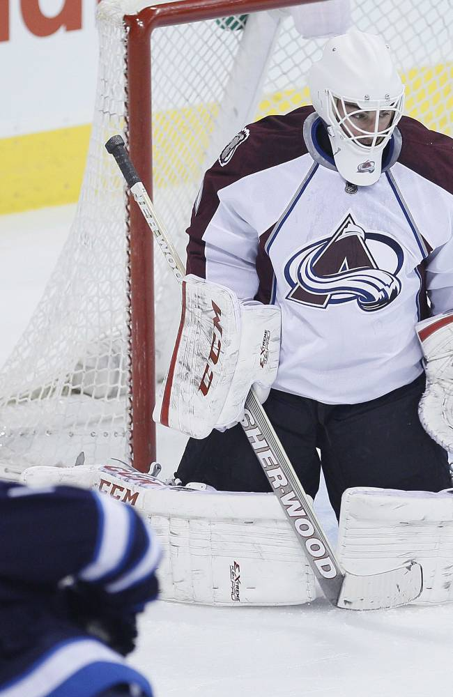 Winnipeg Jets' Andrew Ladd (16) scores on Colorado Avalanche goaltender Reto Berra during the first period of an NHL hockey game Wednesday, March 19, 2014, in Winnipeg, Manitoba