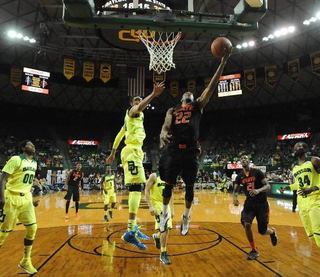 Oklahoma State guard Markel Brown (22) drives to the basket past Baylor center Isaiah Austin (21), left, in the second half of an NCAA college basketball game against Baylor, Monday, Feb. 17, 2014, in Waco, Texas. Baylor won in overtime 70-64
