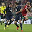 Bayern's Arjen Robben, right, is challenged by Manchester United's Wayne Rooney, left, and Michael Carrick during the Champions League quarterfinal second leg soccer match between Bayern Munich and Manchester United in the Allianz Arena in Munich, Germany