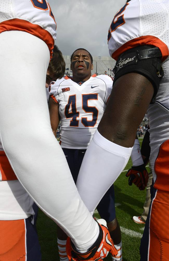 In this Nov. 2, 2013 file photo, Illinois linebacker Jonathan Brown prays with teammates before an NCAA college football game against Penn State in State College, Pa. Brown is in his senior season at Illinois, and is the Big Ten's leading tackler. But he wants to leave a positive stamp on this team after an up-and-down first three seasons with the Illini