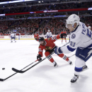 Tampa Bay Lightning center Valtteri Filppula (51) passes the puck to a teammate as Chicago Blackhawks left wing Brandon Saad (20) defends, during the first period of an NHL hockey game Tuesday, Nov. 11, 2014, in Chicago The Associated Press