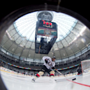 Ottawa Senators' Chris Phillips is seen through a window cut in the boards as he skates with the puck during practice for the Heritage Classic NHL hockey game in Vancouver, British Columbia, on Saturday, March 1, 2014. The Senators are scheduled to play t