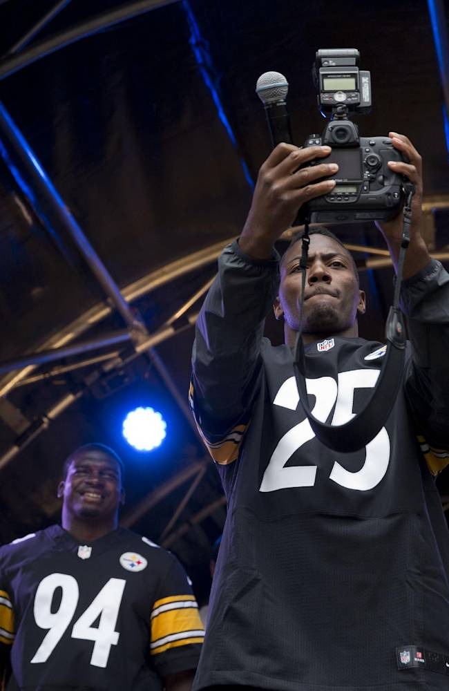 Pittsburgh Steelers' safety Ryan Clark takes a picture of himself with a camera he carried out with him on stage flanked by chairman Dan Rooney, right, head coach Mike Tomlin, left, linebacker Lawrence Timmons, 94 and quarterback Ben Roethlisberger, 7, during an NFL fan rally event in Regent Street, London, Saturday, Sept. 28, 2013.  The Minnesota Vikings are to play the Pittsburgh Steelers at Wembley stadium in London on Sunday, Sept. 29 in a regular season NFL game