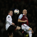 West Ham United's James Collins, right, competes with Manchester United's Wayne Rooney during their English Premier League soccer match at Upton Park, London, Saturday, March 22, 2014