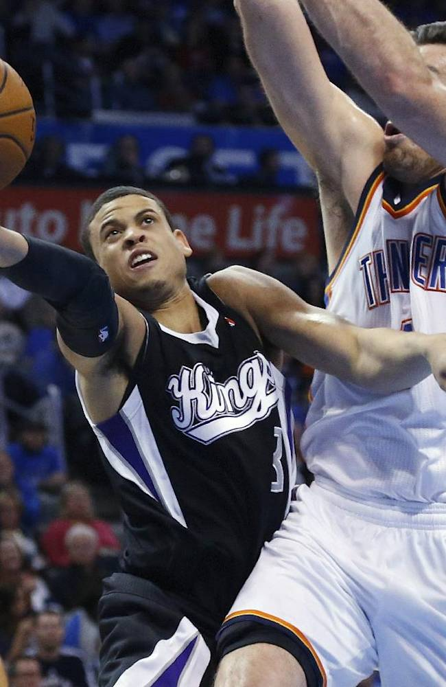 Sacramento Kings guard Ray McCallum (3) shoots in front of Oklahoma City Thunder forward Nick Collison during the second quarter of an NBA basketball game in Oklahoma City, Friday, March 28, 2014