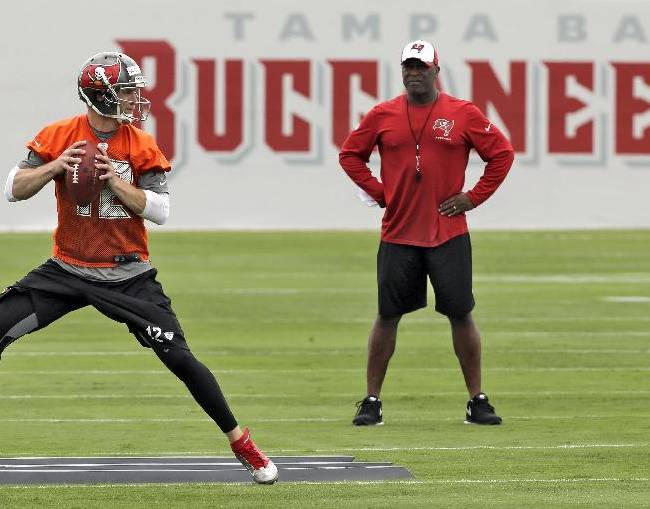New Tampa Bay Buccaneers head coach Lovie Smith, right, watches quarterback Josh McCown run through drills during a voluntary minicamp football practice Tuesday, April 22, 2014, in Tampa, Fla