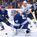 Toronto Maple Leafs goalie Jonathan Bernier (45) makes a save as Maple Leafs Morgan Rielly (4) and Vancouver Canucks forward Radim Vrbata (17) drive to the net during third period NHL hockey action in Toronto on Saturday, Dec. 6, 2014 The Associated Press