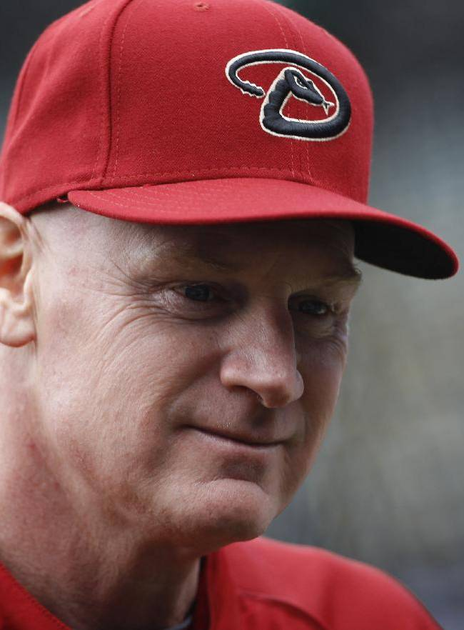 In this April 20, 2013 file photo, Arizona Diamondbacks third base coach Matt Williams chats with William Geivett, assistant general manager of the Colorado Rockies, before the first inning of a Major League Baseball game in Denver. Williams is the new manager of the Washington Nationals. The Nationals will hold a news conference Friday to introduce Williams as the team's fifth manager since it moved to Washington from Montreal in 2005. He replaces Davey Johnson, who is retiring