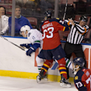 Vancouver Canucks' Radim Vrbata (17) and Florida Panthers' Willie Mitchell (33) slam into a game official during the second period of an NHL hockey game in Sunrise, Fla., Monday, Jan. 19, 2015 The Associated Press