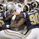 Oakland Raiders quarterback Derek Carr, center, is sacked for an 8-yard loss by St. Louis Rams defensive end William Hayes, left, as Rams' defensive tackle Michael Brockers (90) gets in on the play during the third quarter of an NFL football game Sunday,