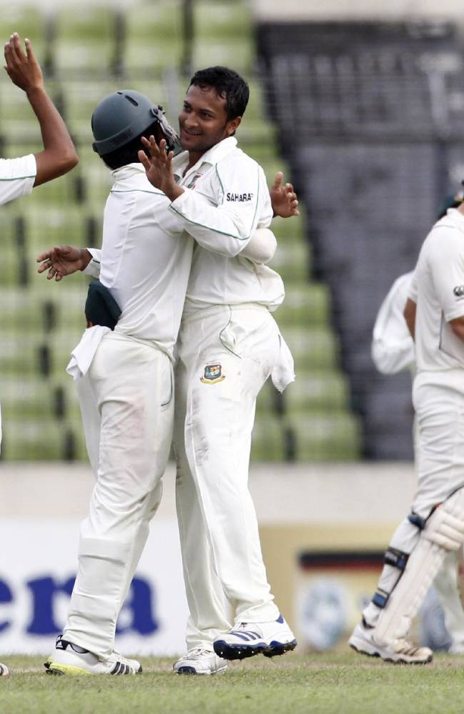 Bangladesh's Shakib Al Hasan, center, is congratulated by teammates for the dismissal of New Zealand's Doug Bracewell during the third day of their second cricket test match in Dhaka, Bangladesh, Wednesday, Oct. 23, 2013