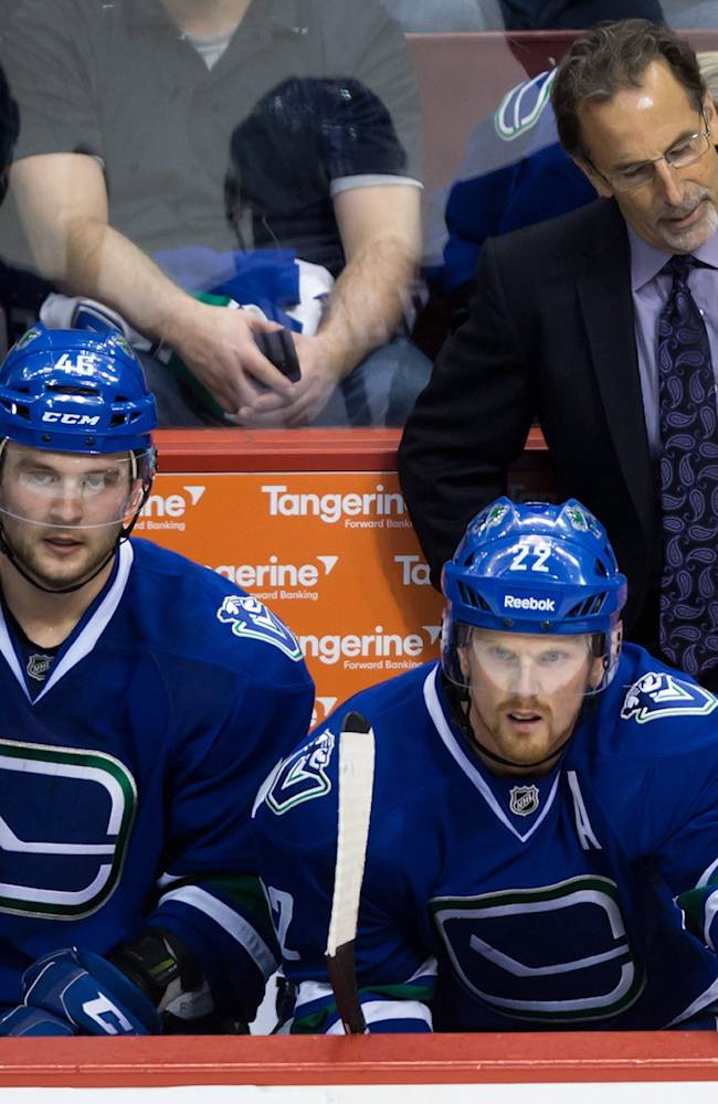 Vancouver Canucks coach John Tortorella, right, reacts after the Colorado Avalanche scored their fourth goal as Nicklas Jensen, left, of Denmark, and Daniel Sedin, of Sweden, sit on the bench during the third period of an NHL hockey game Thursday, April 10, 2014, in Vancouver, British Columbia