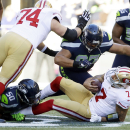 San Francisco 49ers quarterback Colin Kaepernick is sacked by Seattle Seahawks defensive tackle Jordan Hill (97) and outside linebacker K.J. Wright (50) in the first half of an NFL football game against the Seattle Seahawks, Sunday, Dec. 14, 2014, in Seat