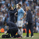 Manchester City's Edin Dzeko, centre, is treated after suffering a cut during his team's 2-1 loss to Wigan's in their English FA Cup quarterfinal soccer match at the Etihad Stadium, Manchester, England, Sunday, March 9, 2014