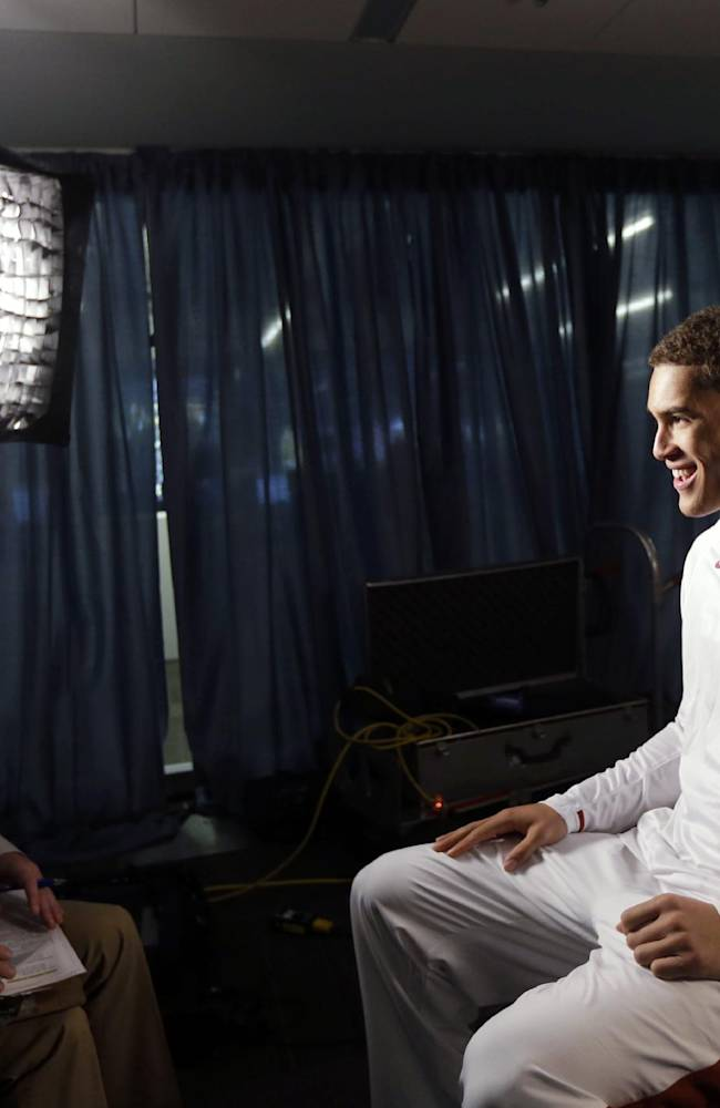 Stanford's Dwight Powell, right, smiles as he takes part in a television interview during the Pac-12 NCAA college basketball media day, Thursday, Oct. 17, 2013, in San Francisco