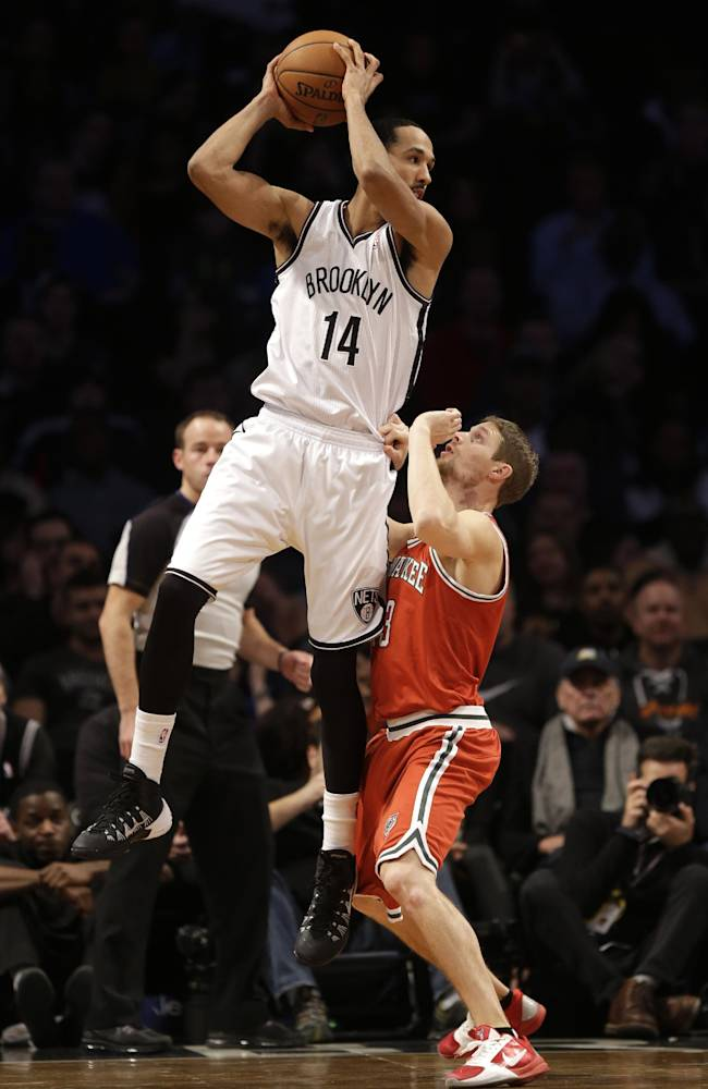 Brooklyn Nets' Shaun Livingston (14) catches a pass over Milwaukee Bucks' Luke Ridnour during the first half of an NBA basketball game at the Barclays Center, Friday, Dec. 27, 2013, in New York
