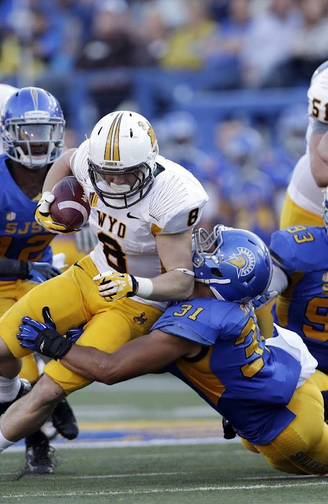 Wyoming running back Brandon Miller (8) is brought down by San Jose State linebacker Keith Smith (31) during the first half of an NCAA college football game on Saturday, Oct. 26, 2013, in San Jose, Calif