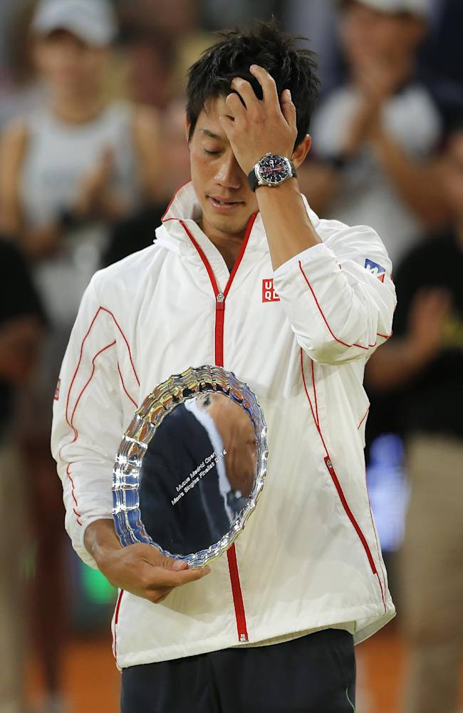 Kei Nishikori from Japan gestures, as he holds his runner up trophy, after the Madrid Open tennis tournament, men's final match against Rafael Nadal from Spain in Madrid, Spain, Sunday, May 11, 2014