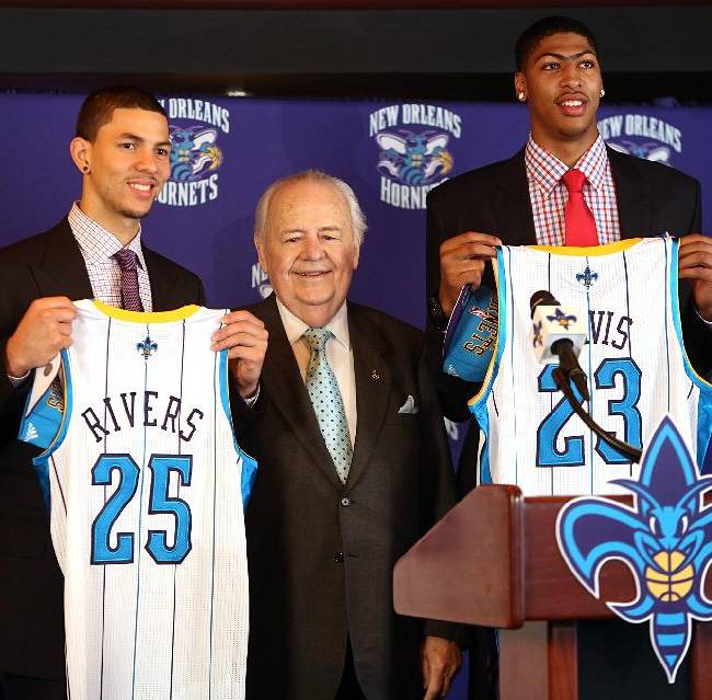 In this June 29, 2012 file photo, New Orleans Hornets NBA basketball team owner Tom Benson is flanked by 2012 draft picks Austin Rivers, left, and Anthony Davis in New Orleans. One of the people most responsible for bringing NBA All-Stars back to the Big Easy this weekend is an 86-year-old man who wasn't that into basketball for much of his life. He is Tom Benson. And in New Orleans, NBA fans and community leaders are grateful the Pelicans owner finally came around