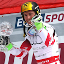 Marcel Hirscher, of Austria, poses for photographers as he holds the alpine ski, men's World Cup slalom discipline trophy, at the World Cup finals in Meribel, France, Sunday, March 22, 2015. (AP Photo/Armando Trovati)