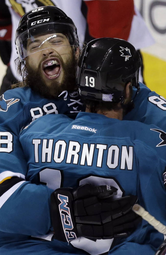 San Jose Sharks' Brent Burns (88) celebrates with teammate Joe Thornton after scoring  the go-ahead goal during the third period of an NHL hockey game against the Ottawa Senators on Saturday, Oct. 12, 2013, in San Jose, Calif. San Jose won 3-2