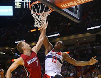 MIAMI, FL - DECEMBER 19: Kevin Seraphin #13 of the Washington Wizards dunks over Justin Hamilton #7 of the Miami Heat during a game  at American Airlines Arena on December 19, 2014 in Miami, Florida. NOTE TO USER: User expressly acknowledges and agrees that, by downloading and/or using this photograph, user is consenting to the terms and conditions of the Getty Images License Agreement. Mandatory copyright notice:  (Photo by Mike Ehrmann/Getty Images)