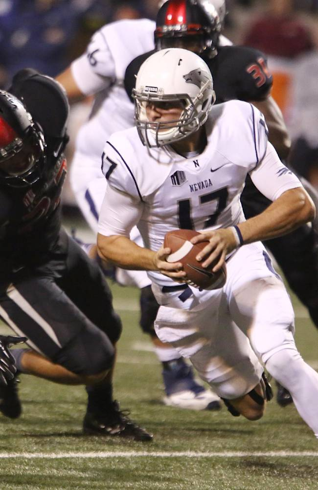 Nevada's Cody Fajardo scrambles out of the pocket against Fresno State defenders in the first half of an NCAA college football game in Fresno, Calif., Saturday, Nov. 2, 2013