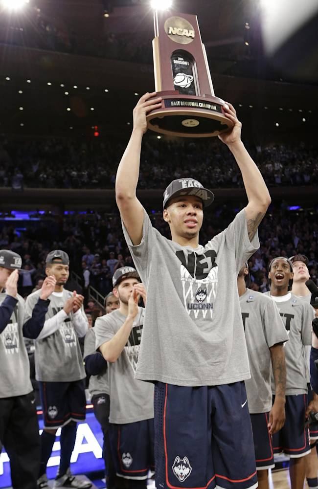 Connecticut's Shabazz Napier holds the championship trophy after a regional final against Michigan State in the NCAA college basketball tournament  Sunday, March 30, 2014, in New York. Connecticut won the game 60-54