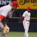 Philadelphia Phillies third baseman Cody Asche, front, watches as a squirrel, which had been making its rounds around the field, dashes toward Phillies shortstop Jimmy Rollins in the fourth inning of a baseball game against the Colorado Rockies in Denver
