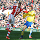 Arsenal's Per Mertesacker, right, fails to prevent Stoke's Peter Crouch shot at goal during the English Premier League soccer match between Stoke City and Arsenal at Britannia Stadium in Stoke On Trent, England, Saturday, March 1, 2014