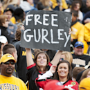 In this Oct. 11, 2014, file photo, a Georgia fan holds a sign in support of Georgia running back Todd Gurley who was suspended earlier this week, during the second quarter of an NCAA college football game against Missouri in Columbia, Mo. Georgia will fil
