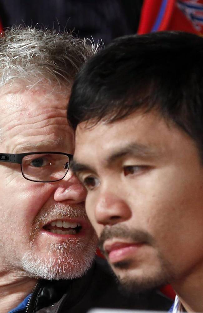 CORRECTS PACQUIAO TO RIGHT, NOT LEFT - Manny Pacquiao, right of the Philippines, right, listens to his trainer Freddie Roach, during a boxing news conference, Tuesday, Feb. 4, 2014, in Beverly Hills, Calif., to promote their upcoming WBO welterweight championship boxing rematch against Tim Bradley. Pacquiao and Bradley's first match on June 9, 2012 was a split decision in favor of Bradley, which ended Pacquiao's welterweight title reign as well as his seven-year, 15-bout winning streak.  Pacquiao vs. Bradley 2 will take place Saturday, April 12, 2014, in Las Vegas