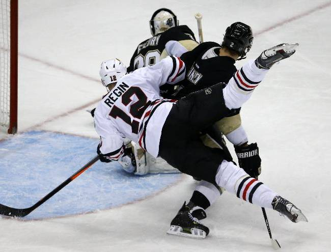 Chicago Blackhawks' Peter Regin (12) collides with Pittsburgh Penguins' Matt Niskanen (2) in the first period of an NHL hockey game in Pittsburgh, Sunday, March 30, 2014