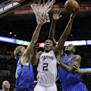 San Antonio Spurs' Kawhi Leonard (2) drives between Dallas Mavericks' Dirk Nowitzki (41), of Germany, and Samuel Dalembert (1) during the first quarter of Game 1 of the opening-round NBA basketball playoff series on Sunday, April 20, 2014, in San Antonio