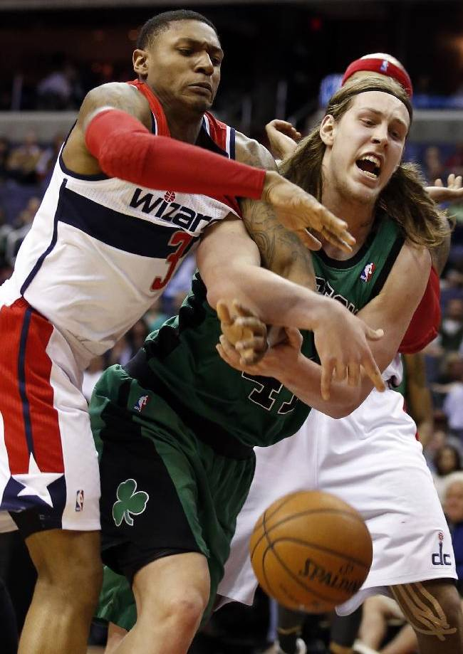 Washington Wizards guard Bradley Beal (3) and Boston Celtics center Kelly Olynyk get tangled up as they go for the ball in the first half of an NBA basketball game Wednesday, April 2, 2014 in Washington