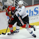 Chicago Blackhawks right wing Kris Versteeg (23) and San Jose Sharks defenseman Brad Stuart (7) battle for the puck during the third period of an NHL hockey game on Sunday, Nov. 17, 2013, in Chicago The Associated Press