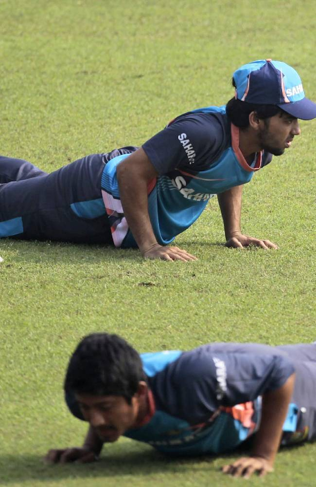 Bangladeshi Mominul Hoque, top, and Anamul Haque perform push-ups during a practice session a day before their third one-day international cricket match against New Zealand in Dhaka, Bangladesh, Saturday, Nov. 2, 2013
