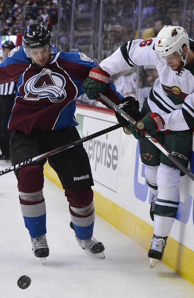 Colorado Avalanche defenseman Nate Guenin (5) checks Minnesota Wild defenseman Marco Scandella (6) into the boards in the first period of Game 2 of an NHL hockey first-round playoff series on Saturday, April 19, 2014, in Denver