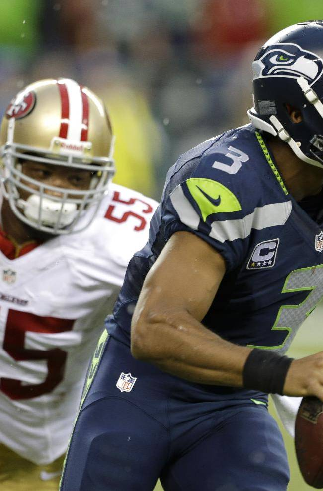 Seattle Seahawks Russell Wilson, right, looks to pass as he is pursued by San Francisco 49ers outside linebacker Ahmad Brooks (55) in the first half of an NFL football game, Sunday, Sept. 15, 2013, in Seattle