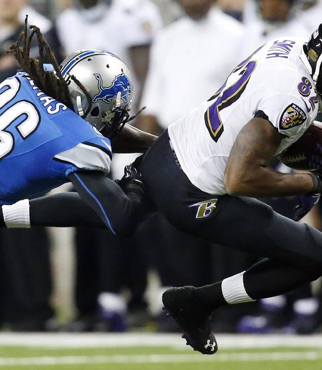 Baltimore Ravens wide receiver Torrey Smith (82) is stopped by Detroit Lions free safety Louis Delmas (26) during the second quarter of an NFL football game in Detroit, Monday, Dec. 16, 2013