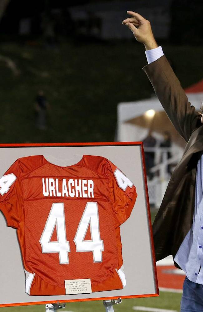 Former New Mexico and Chicago Bears football player Brian Urlacher waves to the crowd as his jersey number is retired during a halftime ceremony at an NCAA college football game against the Air Force on Friday, Nov. 8, 2013, in Albuquerque, N.M