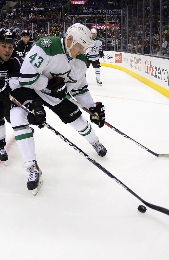 Los Angeles Kings defenseman Willie Mitchell, left, and Dallas Stars right wing Valeri Nichushkin, of Russia, battle for the puck during the third period of their NHL hockey game, Saturday, Oct. 19, 2013, in Los Angeles. The Kings won 5-2