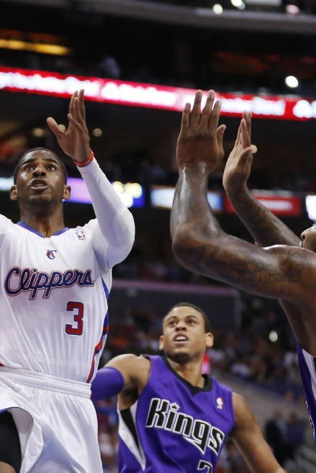 CORRECTS DAY OF WEEK TO SATURDAY - Los Angeles Clippers guard Chris Paul shoots the ball in front of Sacramento Kings guard Ray McCallum, center, and Kings center DeMarcus Cousins, right, during the first half of an NBA basketball game in Los Angeles, Saturday, April 12, 2014