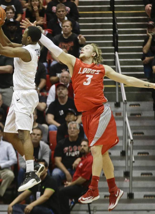 San Diego State guard Xavier Thames gets off a shot as New Mexico guard Hugh Greenwood tries to defend during the second half of a NCAA college basketball game Saturday, March 8, 2014, in San Diego. New Mexico built a 14 point lead only to lose 51-48 and San Diego State captured the Mountain West Conference regular season championship