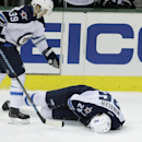 Winnipeg Jets defenseman Tobias Enstrom (39) skates over to check on teammate right wing Blake Wheeler (26) after Wheeler took a hard hit during the third period of an NHL hockey game Monday, March 24, 2014, in Dallas. The Stars won 2-1. Wheeler left the