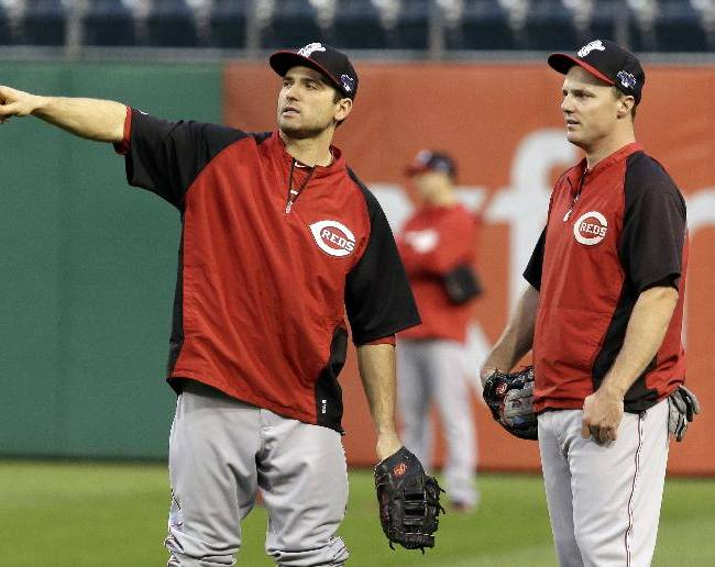 Cincinnati Reds Joey Votto, left, talks with teammate Jay Bruce while standing in the outfield during the baseball team's batting practice in Pittsburgh Monday, Sept. 30, 2013. The Reds are scheduled to face the Pittsburgh Pirates in the National League wild-card game Tuesday in Pittsburgh