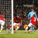 Manchester United's Wayne Rooney, left, grabs the match ball after teammate Robin van Persie, second left, scored their first goal of the game from the penalty spot during the UEFA Champions League last 16 second leg soccer match at Old Trafford, Manchest